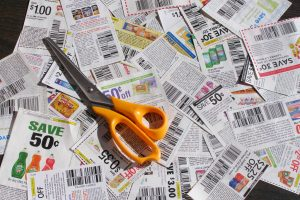 a mass of discount coupons lying on a table with a pair of scissors sitting on top of them