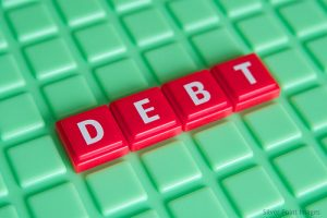 debt spelled out in white letters on raised red plastic squares sitting on alight green plastic background