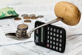 teaspoon balanced on a calculator standing on edge with coins in the spoon and a potato stuck on the other end