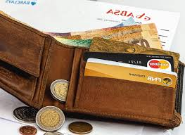 brown wallet lying open showing paper money coins and credit cards