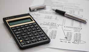 financial calculator sitting on top of financial statements with a pen nearby