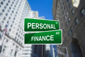 green and white street sign with one sign as personal and the other as finance