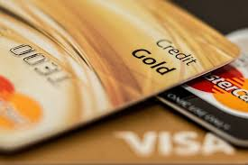 part of a gold credit card lying on top of a visa and a mastercard